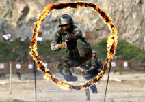 A PLA coastal defence force member jumps through a burning obstacle during a drill to mark the 87th Army Day at a military base in Qingdao...A member of People's Liberation Army (PLA) coastal defence force jumps through a burning obstacle during a drill to mark the 87th Army Day at a military base in Qingdao, Shandong province July 29, 2014. The PLA Army Day falls on August 1 every year. Chinese President Xi Jinping has pledged to strike hard against graft in the military, urging soldiers to banish corrupt practices and ensure their loyalty to the ruling Communist Party, state media reported on Friday. Picture taken July 29, 2014. REUTERS/Stringer (CHINA - Tags: MILITARY POLITICS ANNIVERSARY TPX IMAGES OF THE DAY) CHINA OUT. NO COMMERCIAL OR EDITORIAL SALES IN CHINA